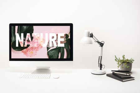 computer with green monstera leaves and roses with nature lettering on monitor on white background