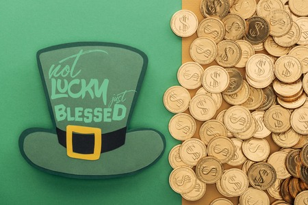 top view of golden coins near paper hat with not lucky just blessed lettering on green background Stock Photo