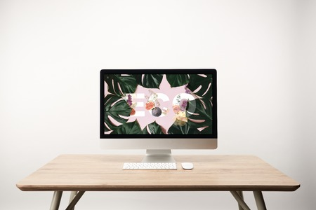 computer with green monstera leaves and eco lettering on monitor on wooden desk Stock Photo