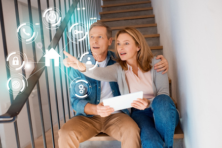wife pointing hand while sitting with husband on stairs and using digital tablet, smart home concept 스톡 콘텐츠