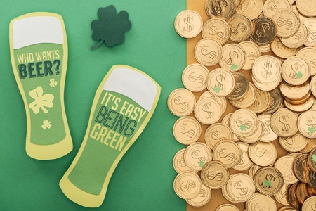 top view of golden coins with dollar signs, shamrock and paper beer glasses with lettering on green background Foto de archivo - 119438569