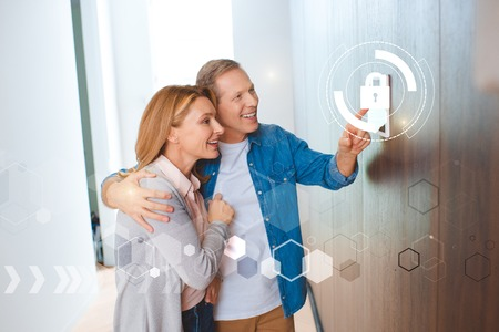 smiling husband pointing at smart house system control panel and hugging happy wife