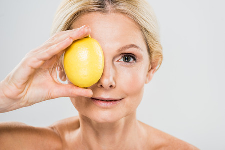 beautiful and mature woman holding ripe lemon and looking at camera isolated on grey