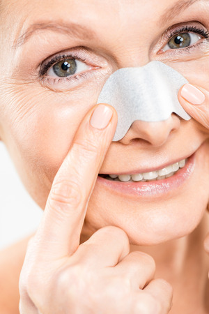 close up of beautiful and mature woman looking at camera with nose strip isolated on white Stock Photo