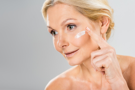 beautiful and mature woman looking away and applying cosmetic cream on face