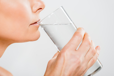 cropped view of mature woman drinking water from glass isolated on grey
