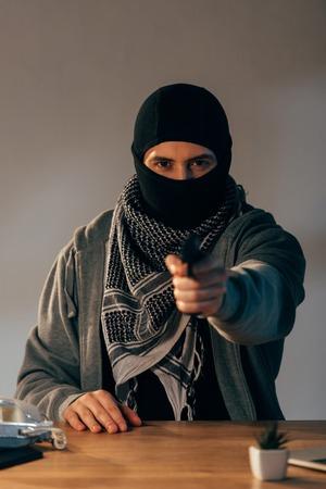 Concentrated criminal in black mask aiming gun at camera
