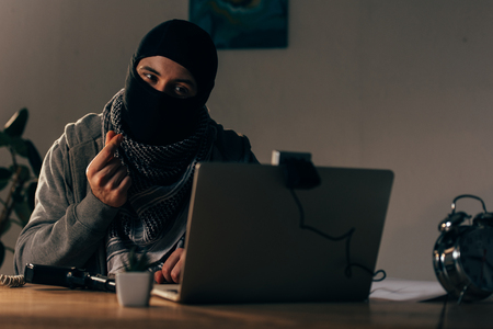 Terrorist in mask looking at webcam and showing money gesture Stock Photo