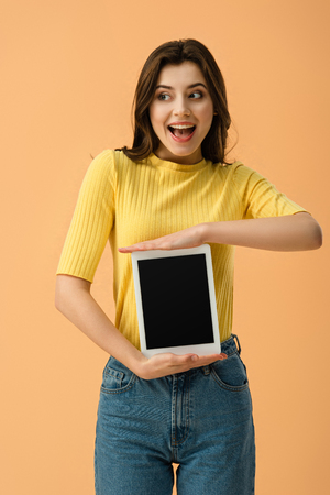 Excited young woman holding digital tablet with blank screen isolated on orange