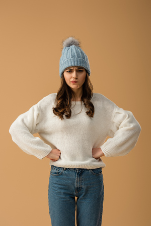 Skeptical brunette girl in white sweater standing with arms akimbo isolated on beige Stock Photo