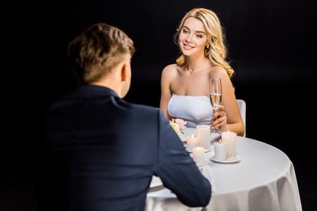 happy couple sitting at served table with burning candles isolated on black