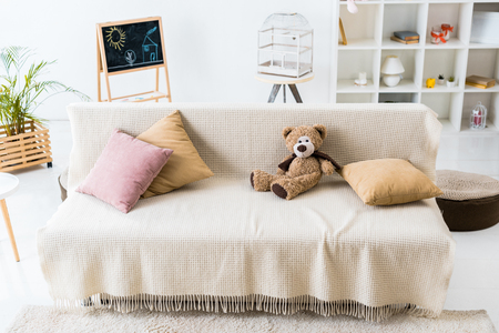cosy living room with pillows and teddy bear assembled on comfortable sofa