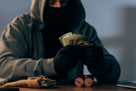 Partial view of terrorist in mask counting dollar banknotes