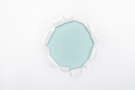 ripped  hole in white textured paper on light blue dotted background
