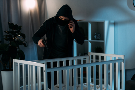 Criminal in mask talking on smartphone and aiming gun in crib