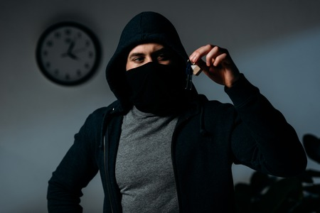 Confident thief in mask and hoodie standing in dark room and looking at keys