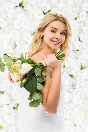 beautiful bride holding wedding bouquet and looking at camera on white floral background