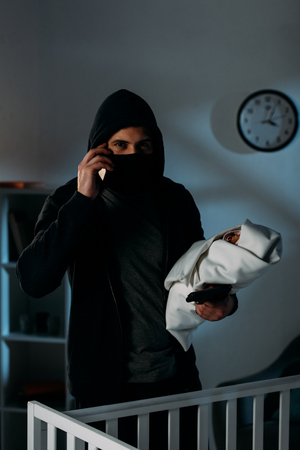 Kidnapper with gun holding infant child and talking on smartphone