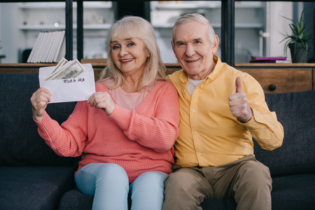 senior couple showing thumb up sign while holding envelope with roth ira lettering and dollar banknotes Stock Photo