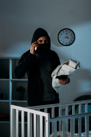 Kidnapper in mask holding infant child and talking on smartphone Stock Photo