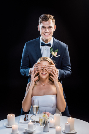 happy groom standing behind smiling bride and closing her eyes with hands isolated on black Stock Photo