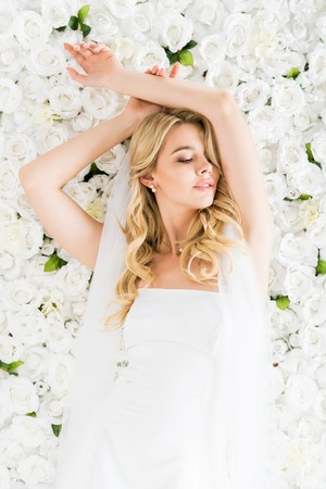 beautiful young bride with closed eyes on white floral background 스톡 콘텐츠