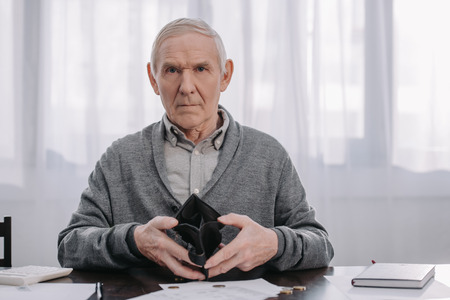 male pensioner sitting at table with paperwork, looking at camera and holding empty wallet