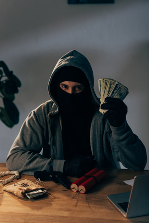 Terrorist in mask and gloves sitting at table with weapon and holding dollar banknotes