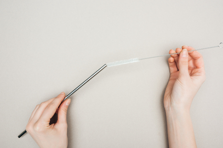 partial view of woman holding cleaning brush and stainless steel straw on grey