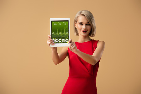 beautiful woman in red dress holding digital tablet with health app on screen isolated on beige Stock Photo