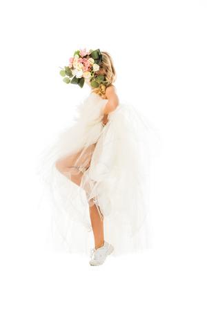 Attraktive junge Frau, die in Hochzeitskleid und Turnschuhen posiert, während sie das Gesicht hinter dem Hochzeitsstrauß isoliert auf weiß versteckt Standard-Bild
