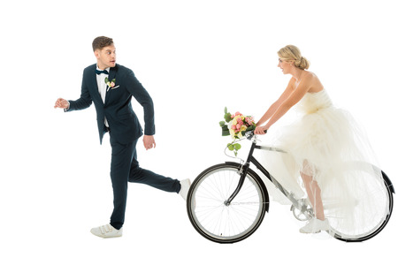 handsome groom in suit and sneakers running from bride on bicycle isolated on white Stock Photo