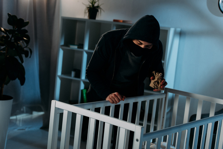 Kidnapper in mask holding money bag and looking in crib Stock Photo