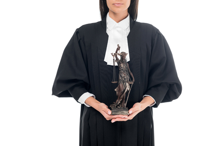 Partial view of judge in judicial robe holding themis figurine isolated on white