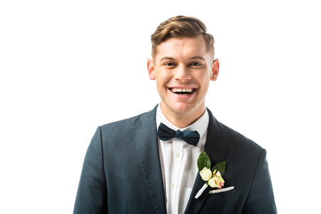 happy handsome bridegroom in bowtie and jacket with boutonniere looking at camera isolated on white
