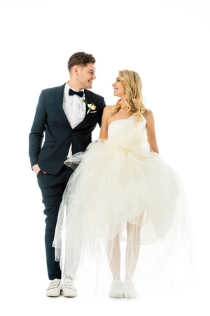 handsome groom and beautiful bride in elegant clothes and sneakers looking at each other isolated on white Stock Photo