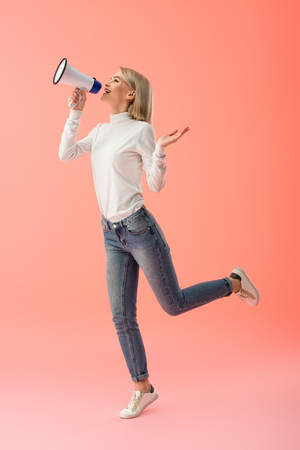 cheerful blonde woman speaking in megaphone on pink background