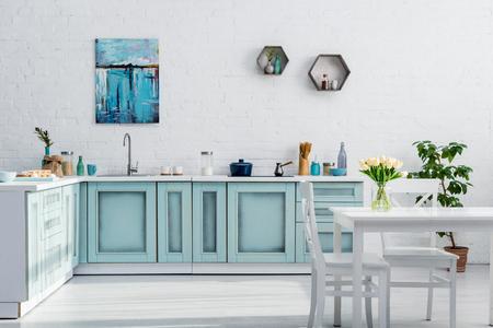 Interieur der türkisfarbenen und weißen Küche voller Sonnenlicht Standard-Bild