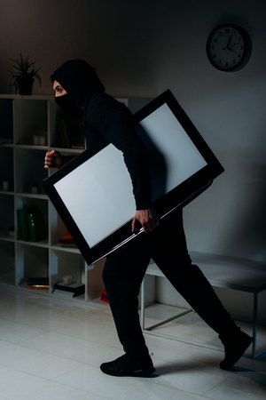 Side view of thief stealing flat-screen tv with blank screen