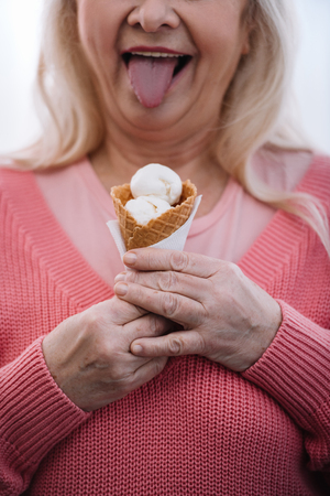 cropped view of senior woman sticking tongue out and holding ice cream cone