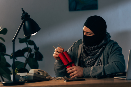 Terrorist in mask with dynamite sitting at table in room