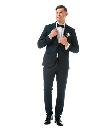 happy bridegroom in elegant black suit with boutonniere isolated on white