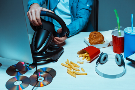 cropped view of man holding steering wheel on table with fast food, discs and headphones