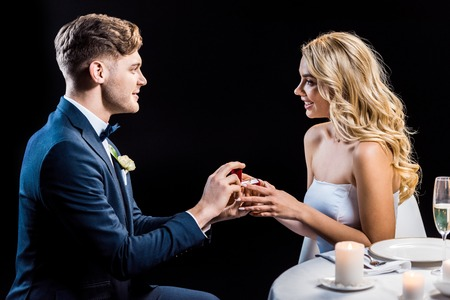 handsome young man making marriage proposal to happy young woman isolated on black