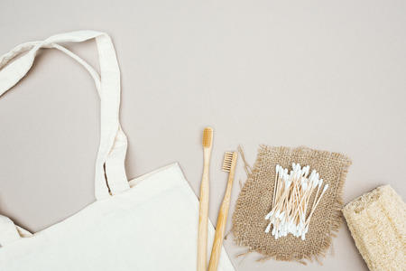 wooden toothbrushes, organic loofah, cotton swabs, sackcloth and white cotton bag on grey background