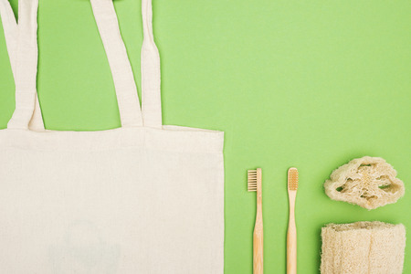 organic bamboo toothbrushes, loofah and cotton bag on light green background