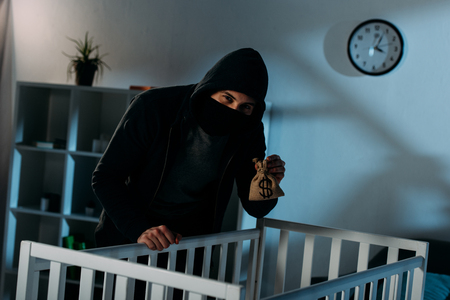 Kidnapper standing near crib with money bag and looking at camera