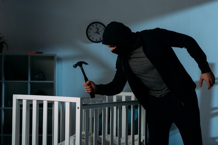 Criminal in mask holding hammer while standing near crib in dark room