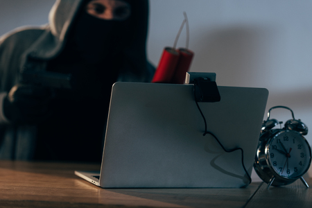 Terrorist in mask holding dynamite while using laptop in dark room