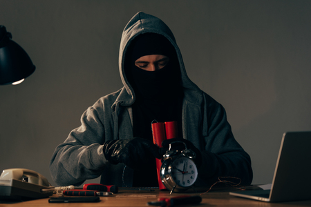 Concentrated terrorist in mask and black gloves making bomb Stock Photo